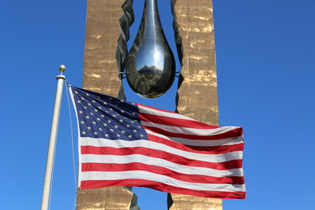 9 11: BAYONNE, NEW JERSEY - NOVEMBER 18: American flag in the front of  September 11 memorial To the Struggle Against World Terrorism by Russian artist Zurab Tsereteli on November 18, 2014 in Bayonne. Editorial