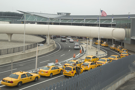 best travel destinations: NEW YORK- MAY 8, 2014: New York Taxi line next to JetBlue Terminal 5 at John F Kennedy International Airport.  JFK is one of the biggest airports in the world with 4 runways and 8 terminals