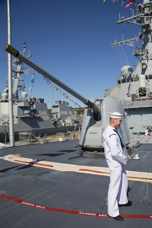 gun shell: NEW YORK - MAY 25, 2014:Unidentified US Navy with gun shell in the front of turret containing a 5-inch gun on the deck of US Navy guided-missile destroyer USS McFaul during Fleet Week 2014 in New York Editorial
