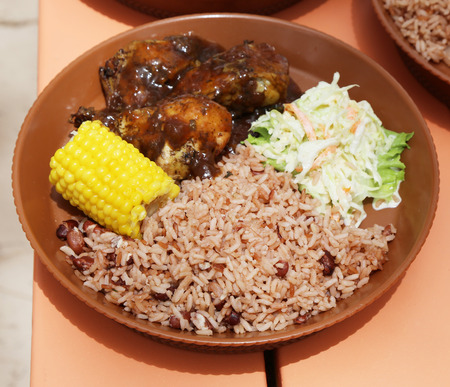 Typical local food at Caribbean Islands: Barbecue chicken, coleslaw salad, corn with black beans and rice