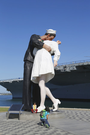 SAN DIEGO, CALIFORNIA - SEPTEMBER 29, 2014: Unidentified family taking picture in the front of the Unconditional Surrender sculpture by Seward Johnson and USS Midway in San Diego