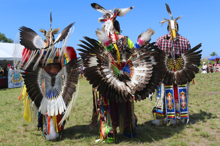regalia: NEW YORK - JUNE 8, 2014: Unidentified male Native American dancers wears traditional Pow Wow dress with Dance Bustle during the NYC Pow Wow in Brooklyn