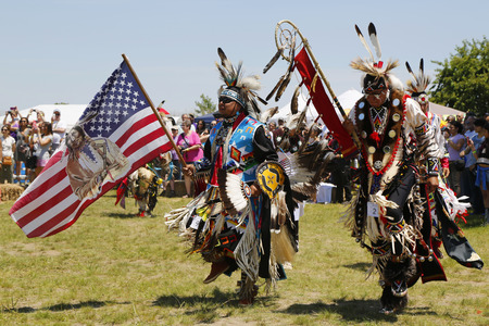 new entry: NEW YORK - JUNE 8, 2014: The Eagle Staff leads the Grand Entry at the NYC Pow Wow in Brooklyn. A pow-wow is a gathering and Heritage Celebration of North America s Native people