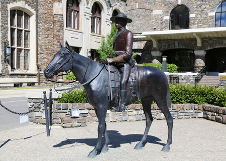 BANFF, CANADA - JULY 26, 2014: Statue Of An Royal Canadian Mounted Police Riding A Horse at Banff Springs Hotel in the Canadian Rockies.
