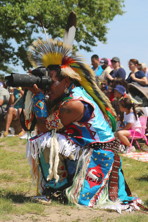 moccasins: NEW YORK - JUNE 8, 2014: Unidentified Native American taking pictures at the NYC Pow Wow in Brooklyn. A pow-wow is a gathering and Heritage Celebration of North America s Native people
