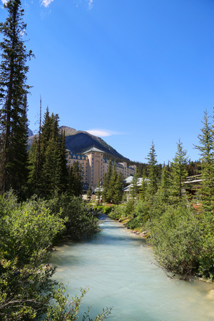 BANFF, CANADA - JULY 28, 2014: Bow river and Banff Springs Hotel in the Canadian Rockies. The Banff Springs Hotel was built during the 19th century in Scottish Baronial style