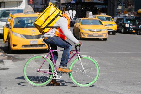 road bike: NEW YORK - FEBRUARY 19, 2015: Unidentified delivery man on bike in Manhattan Editorial