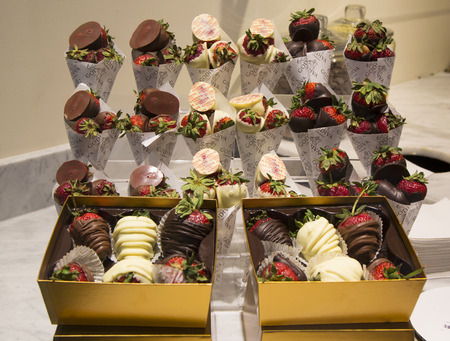 famous industries: LAS VEGAS, NEVADA - MAY 10, 2014: Milk and Dark Chocolate Dipped Strawberries by Godiva on display in Las Vegas. Godiva Chocolatier is a manufacturer of premium chocolates founded in Belgium in 1926. Editorial
