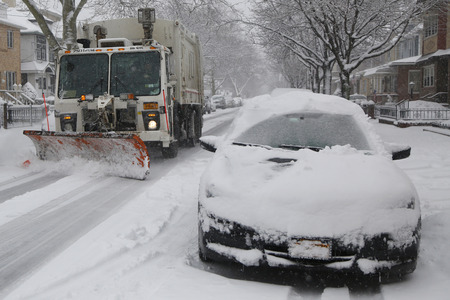 inconvenient: BROOKLYN, NEW YORK - MARCH 5, 2015: New York Department of Sanitation truck cleaning streets in Brooklyn, NY during massive Winter Storm Thor