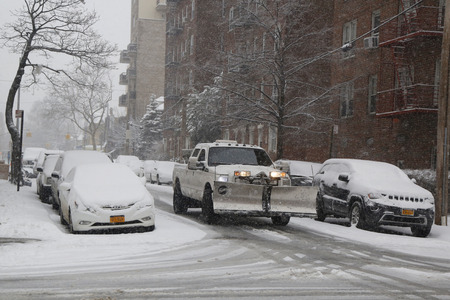 inconvenient: BROOKLYN, NEW YORK - MARCH 5, 2015: Snow plow truck in Brooklyn, NY during massive Winter Storm Thor Editorial