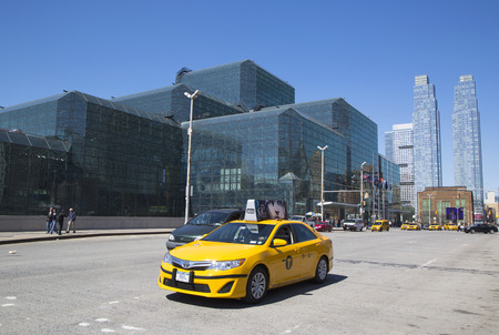 NEW YORK - APRIL 24, 2014: Yellow taxi in front of Javits Convention Center in Manhattan. The convention center has a total area space of 1,800, 000 square ft and has 840,000 square ft of total space