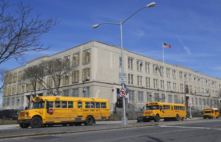 public schools: BROOKLYN, NEW YORK - MARCH 19, 2015: School buses in the front of public school in Brooklyn. New York City has the largest school transportation department in the country. Editorial