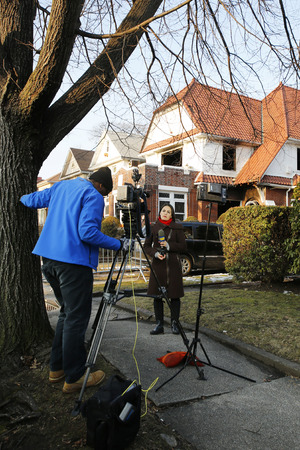 jewish home: BROOKLYN, NEW YORK - MARCH 21, 2015: TV Channel 12 reporter in the front of burnt house after fire sparked by hot plate killed seven children in Midwood, Brooklyn
