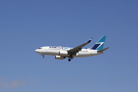 descending: SAN DIEGO, CALIFORNIA - SEPTEMBER 27, 2014: WestJet Airlines Boeing 737 plane descending for landing San Diego International Airport. Editorial