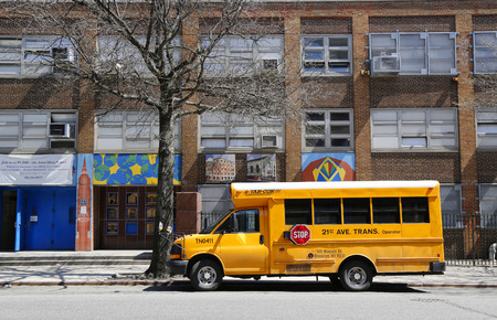 NEW YORK - APRIL 14, 2015:  School bus in front of public school in Manhattan