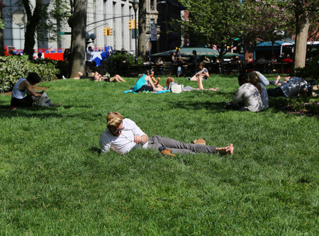 NEW YORK CITY - MAY 7, 2015: Locals and tourists crowded the Union Square Park in New York to enjoy the nice weather and take a sunbath