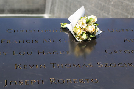 11: NEW YORK - JULY 11, 2015: Flowers left at the National September 11 Memorial at Ground Zero in Lower Manhattan