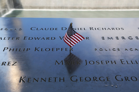 11: NEW YORK - JULY 11, 2015: American flag left at the National September 11 Memorial  at Ground Zero in Lower Manhattan Editorial