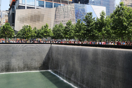 11: NEW YORK - JULY 11, 2015: National September 11 Memorial Museum and Reflection Pool with Waterfall in September 11 Memorial Park