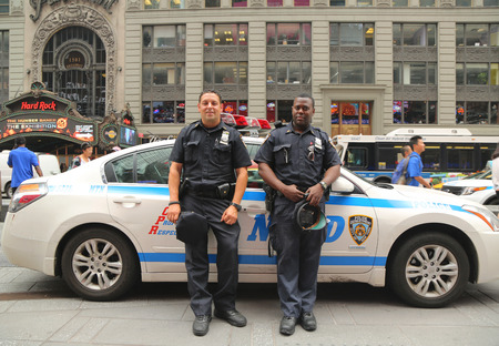 NEW YORK - JULY 9, 2015: NYPD officers providing security at the Times Square. New York Police Department, established in 1845, is the largest police force in USA