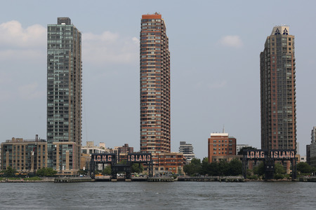 industrial park: NEW YORK - JULY 5, 2015: Long Island City waterfront with historic steel railroad gantries at Hunters Point in Queens. These landmarks were once used to load and unload rail car floats and barges