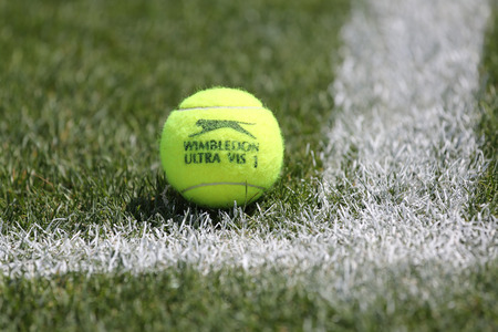 NEW YORK - AUGUST 7, 2015: Slazenger Wimbledon Tennis Ball on grass tennis court. Slazenger Wimbledon Tennis Ball exclusively used and endorsed by The Championships, Wimbledon