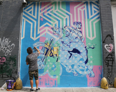 NEW YORK - AUGUST 8, 2015: Street artist painting mural in Little Italy during LoMan Arts Festival in Manhattan