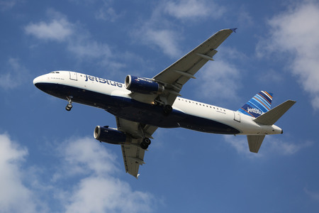jetblue: NEW YORK - AUGUST 13, 2015: JetBlue Airbus A320 descending for landing at JFK International Airport in New York