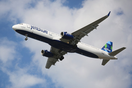 jetblue: NEW YORK - AUGUST 13, 2015: JetBlue Airbus A321 descending for landing at JFK International Airport in New York