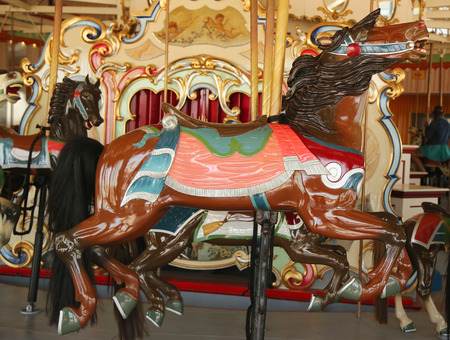 coney: BROOKLYN, NEW YORK - JUNE 7, 2015: Horses on a traditional fairground BB carousel at historic Coney Island Boardwalk in Brooklyn Editorial