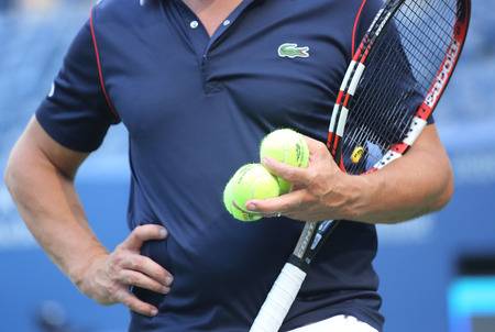 racket stadium: NEW YORK - AUGUST 25, 2015: Tennis coach holding US Open Wilson tennis balls at Billie Jean King National Tennis Center in New York. Wilson is the Official Ball of the US Open since 1979
