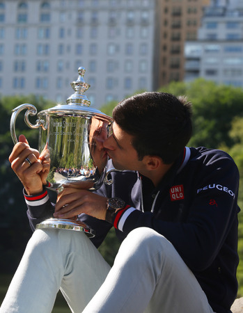 serbia: NEW YORK - SEPTEMBER 14, 2015: Ten times Grand Slam champion Novak Djokovic posing in Central Park with championship trophy after victory at US Open 2015 Editorial