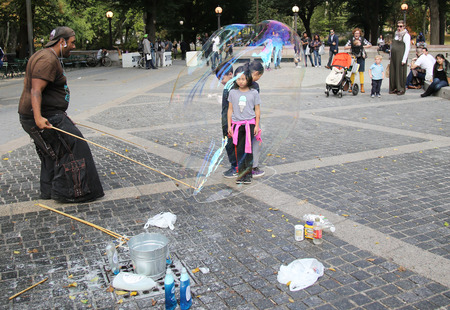 oversize: NEW YORK CITY - OCTOBER 9, 2015: Street performer creating oversize bubbles for kids at Central Park in New York Editorial