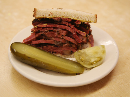 deli: Famous Pastrami on rye sandwich served with pickle in New York Deli Stock Photo