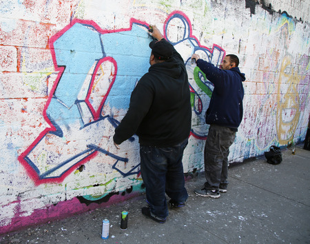 collectives: NEW YORK - NOVEMBER 8, 2015: Street artists painting mural at East New York in Brooklyn. A mural is any piece of artwork painted or applied directly on a wall, ceiling or other large permanent surface