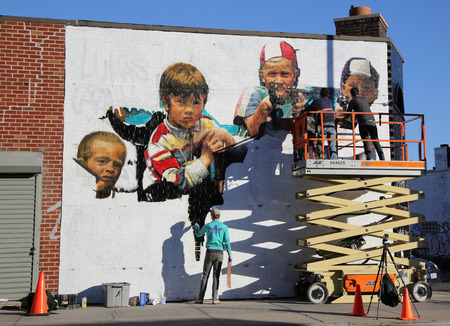 NEW YORK - NOVEMBER 8, 2015 Street artists painting mural at Williamsburg in Brooklyn. A mural is any piece of artwork painted or applied directly on a wall, ceiling or other large permanent surface Sajtókép