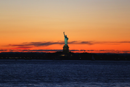 liberty torch: NEW YORK - AUGUST 22, 2015: The Statue of Liberty in New York Harbor at sunset