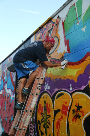 NEW YORK - AUGUST 29, 2015: Street artist painting mural at East New York in Brooklyn. A mural is any piece of artwork painted or applied directly on a wall, ceiling or other large permanent surface