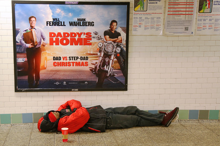 homeless person: NEW YORK - DECEMBER 13, 2015: Scene at Times Square Subway station in Midtown Manhattan.Times Square is a major commercial intersection and a neighborhood in Midtown Manhattan. Homeless person