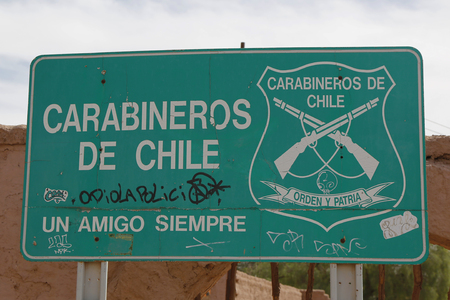 police force: SAN PEDRO DE ATACAMA, CHILE - APRIL 10, 2015: Carabineros de Chile sign on the street at San Pedro de Atacama. The Carabiniers of Chile are the uniformed Chilean national police force and gendarmerie.