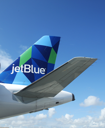best travel destinations: PUNTA CANA, DOMINICAN REPUBLIC - JANUARY 4, 2016: JetBlue Airbus A321 prism inspired design tailfin at Punta Cana International Airport