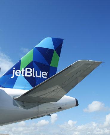 jetblue: PUNTA CANA, DOMINICAN REPUBLIC - JANUARY 4, 2016: JetBlue Airbus A321 prism inspired design tailfin at Punta Cana International Airport