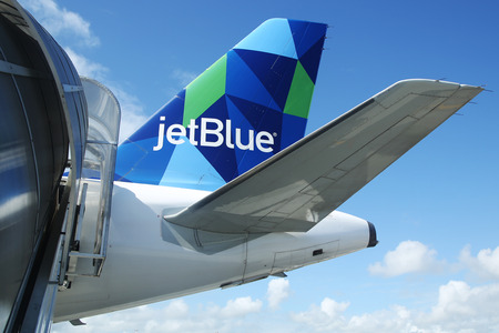 cana: PUNTA CANA, DOMINICAN REPUBLIC - JANUARY 4, 2016: JetBlue Airbus A321 prism inspired design tailfin at Punta Cana International Airport