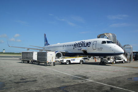 cana: PUNTA CANA, DOMINICAN REPUBLIC - JANUARY 4, 2016: Jetblue Airlines Embraer 190 on tarmac at Punta Cana International Airport. The Dominican Republic is the most visited destination in the Caribbean
