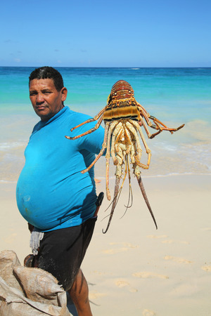 PUNTA CANA, DOMINICAN REPUBLIC - JANUARY 3, 2016: Local fisherman with morning catch at Bavaro Beach in Punta Cana