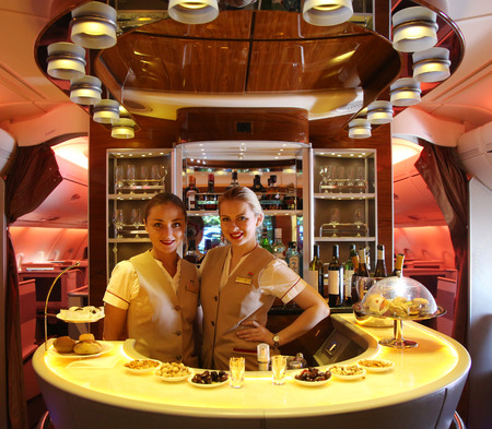 flight crew: DUBAI, UAE - FEBRUARY 7, 2016: Emirates Airbus A380 in flight cocktail bar and lounge. Emirates is one of two flag carriers of the United Arab Emirates along with Etihad Airways and is based in Dubai