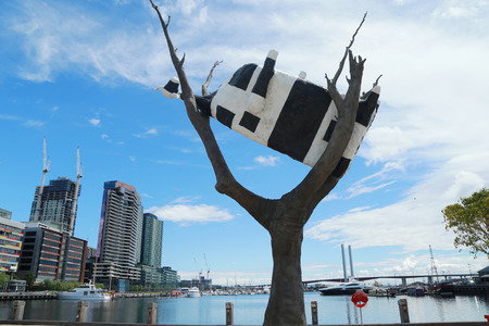 MELBOURNE, AUSTRALIA - JANUARY 31, 2016:Iconic sculpture Cow up a Tree by John Kelly in Docklands section in Melbourne. 8-metre high, four ton bronze sculpture originally installed in February 2001. Editorial