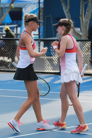 doubles: MELBOURNE, AUSTRALIA - JANUARY 30, 2016: Junior tennis players Dayana YastremskaL and Anastasia Zarytska of Ukraine in action during her doubles final match at Australian Open 2016 in Melbourne Park Editorial