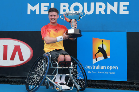 racket stadium: MELBOURNE, AUSTRALIA - JANUARY 30, 2016: Grand Slam champion Gordon Reid of Great Britain posing with trophy after Australian Open 2016 wheelchair singles final match in Melbourne Park