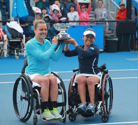 30 s: MELBOURNE, AUSTRALIA - JANUARY 30, 2016: Marjolein Buis of Netherlands L and Yui Kamiji of Japan posing with trophy after victory Australian Open 2016 women s wheelchair doubles final match